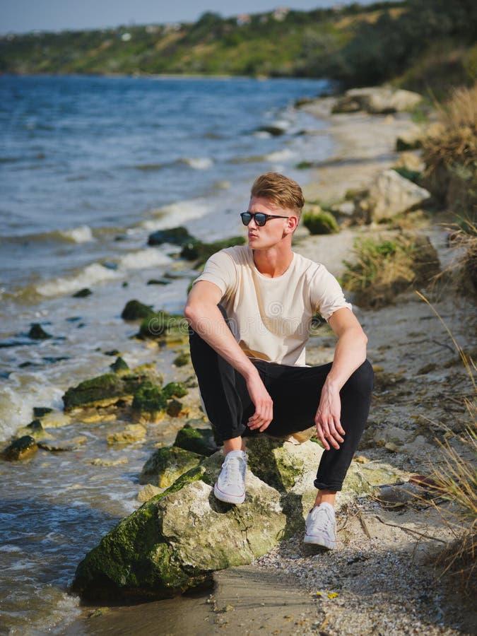 Stilig man som sitter nära vatten En fundersam grabb på en suddig naturlig bakgrund Manligt förtroendebegrepp kopiera avstånd arkivbild