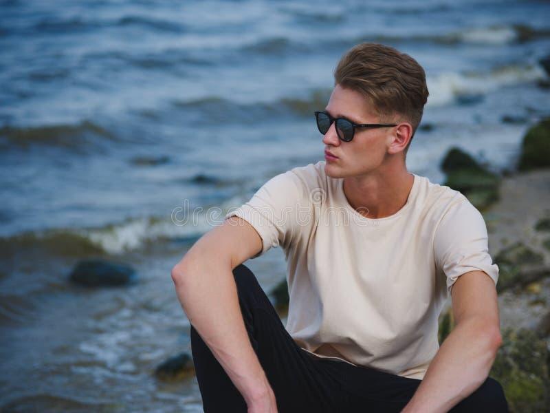 Stilig man som sitter nära vatten En fundersam grabb på en suddig naturlig bakgrund Manligt förtroendebegrepp kopiera avstånd royaltyfri fotografi