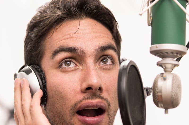 Stilig man som sjunger i musikstudio arkivfoton
