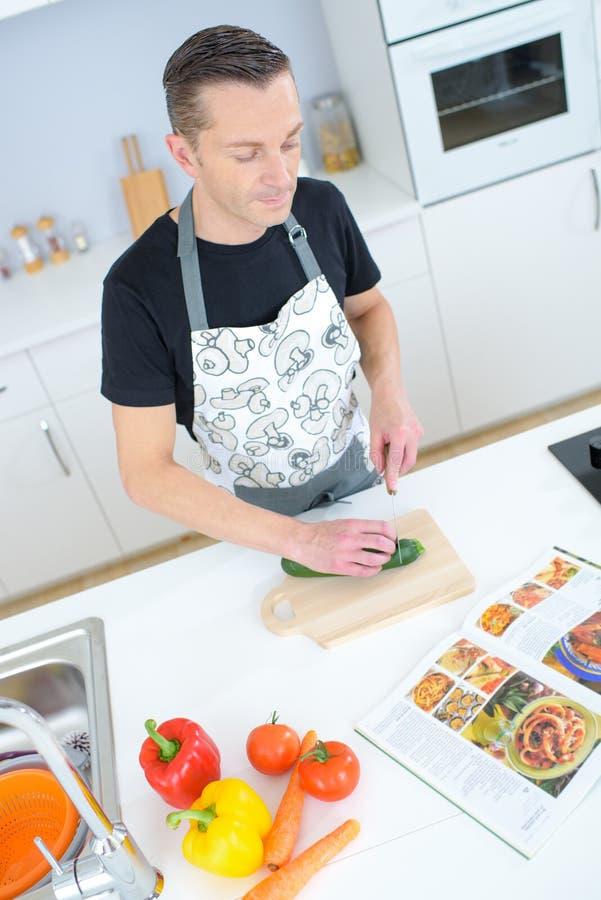 Stilig man som skivar grönsaker i kök arkivbilder