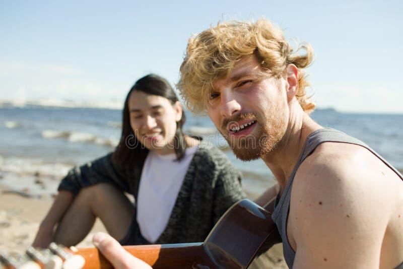 Stilig man som spelar gitarren nära vän royaltyfri fotografi