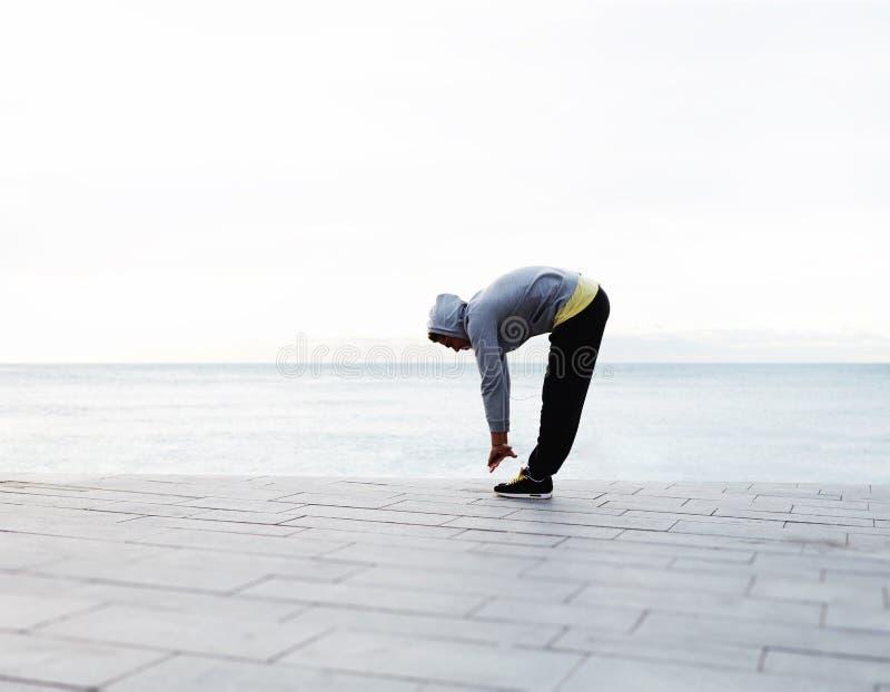 Stilig man som sträcker, innan att jogga arkivbild