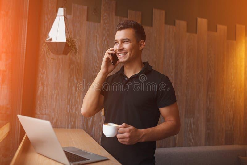 Stilig man som talar på mobiltelefonen, medan rymma kaffekoppen arkivbild