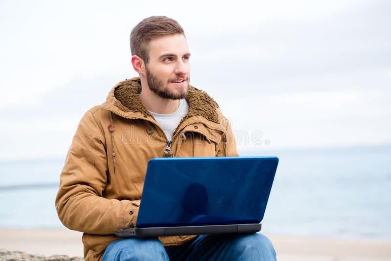 Stilig man som utomhus använder bärbar datordatoren royaltyfria foton