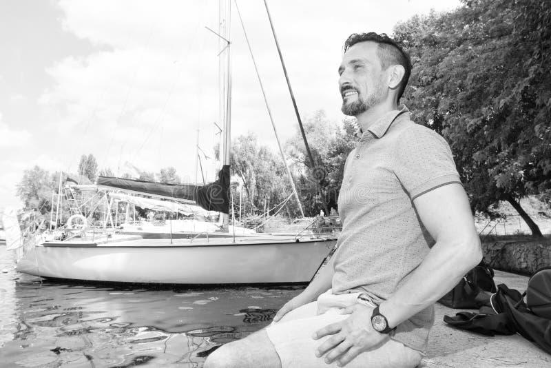 stilig man som utomhus poserar på fartygbakgrund Man att koppla av och att tycka om sikten i natur och sjön royaltyfria bilder