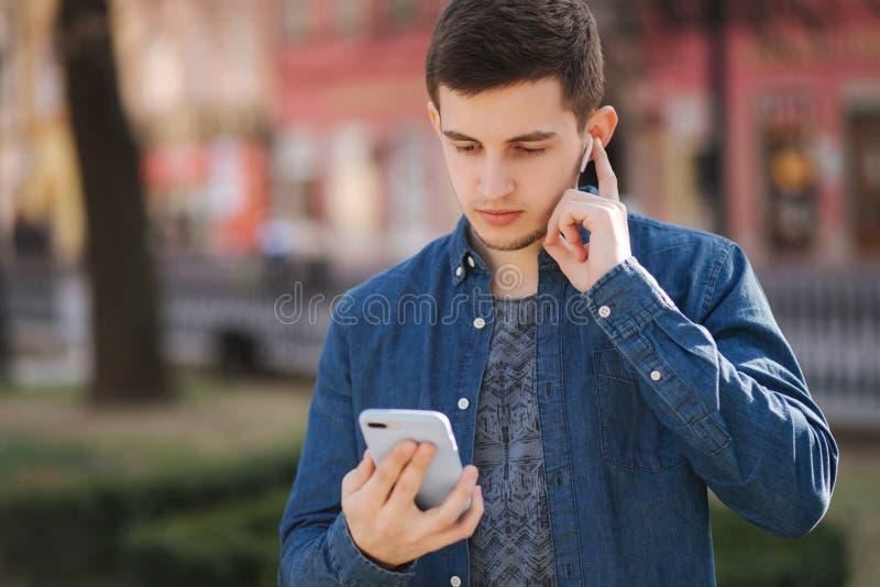 Stilig manbrukstelefon och trådlös hörlurar för att prata för video Video appell arkivfoto