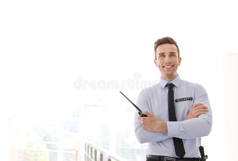 Stilig manlig ordningsvakt med sändaren för bärbar radio inomhus royaltyfria bilder