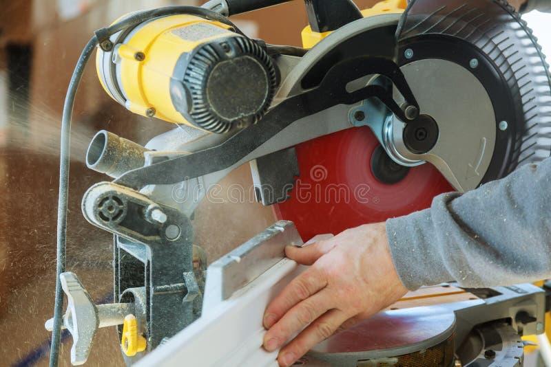 stilig mansnickare som använder en cirkelsåg, medan installera trä arkivfoto