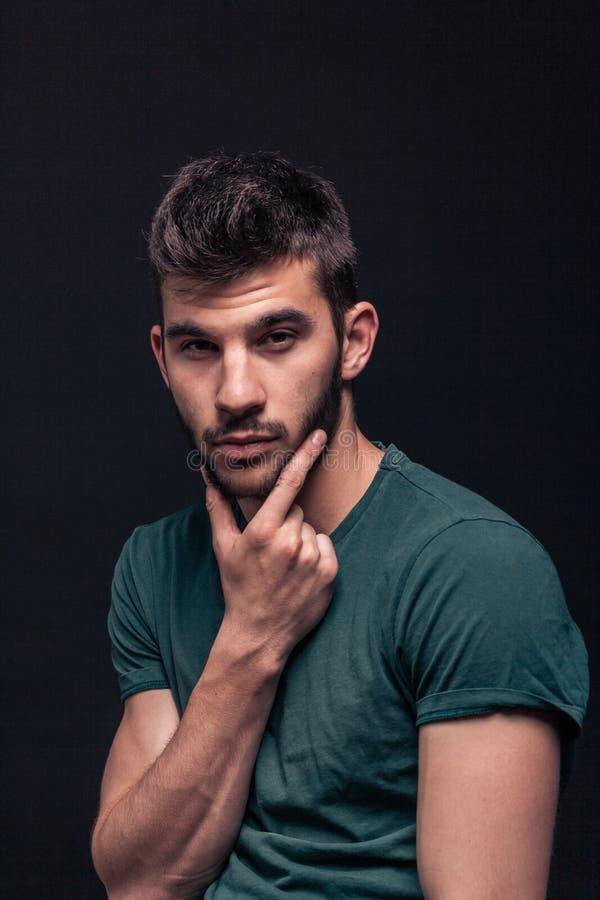 Stilig manstående, hand på skägg arkivfoton