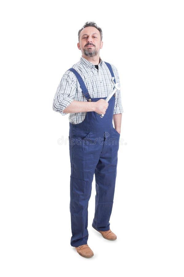 Stilig mekaniker eller repairman med anseende och att posera för skruvnyckel arkivbild