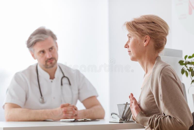 Stilig mellersta ålderdoktor och kvinnlig patient på sjukhuskontoret royaltyfria bilder