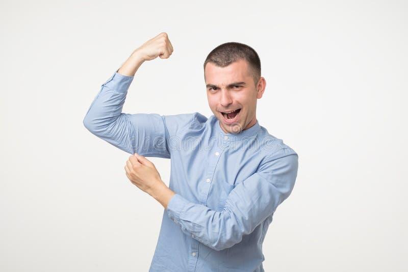 Stilig mellersta ålderman i blå skjorta som pekar biceps som uttrycker styrka och sunt liv royaltyfri foto