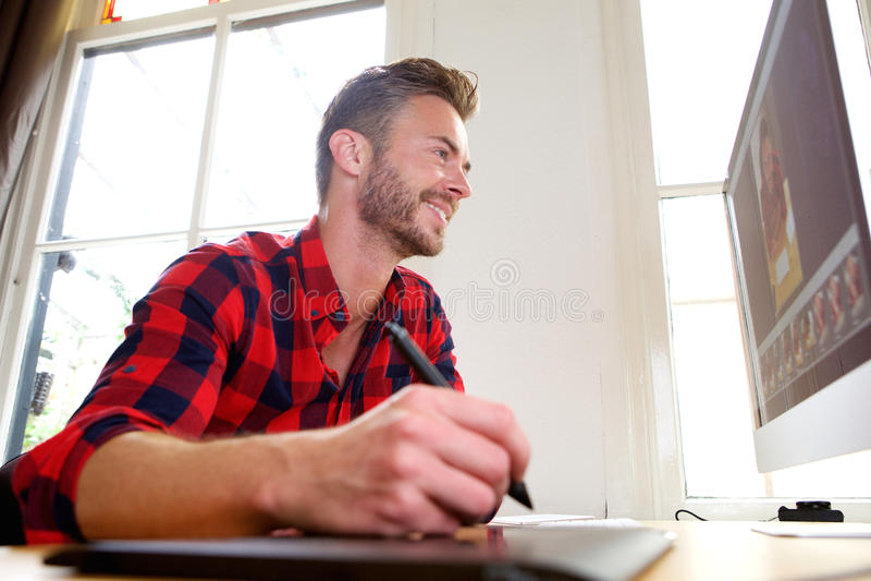 Stilig mellersta ålderman på skrivbordet med nålen och skrivbordet fotografering för bildbyråer
