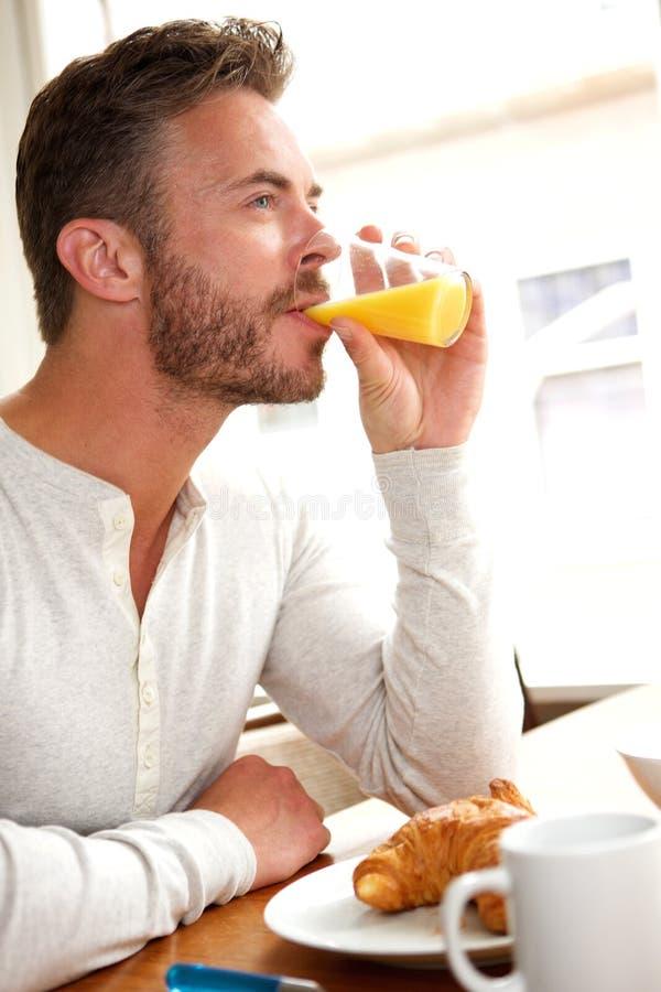 Stilig mellersta ålderman som dricker fruktsaft med frukosten royaltyfria foton