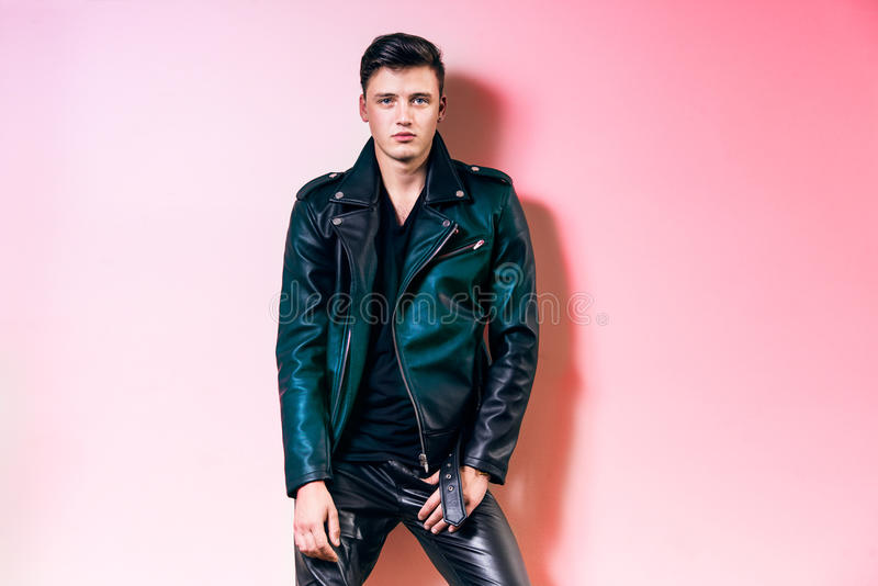 Stilig modemanstående, härligt manligt omslag, flåsande och t-skjorta för läder för modellklädersvart som poserar nära väggen arkivbild