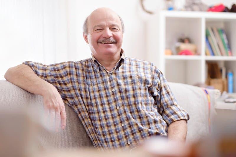 Stilig mogen latinamerikansk man som sitter på soffan arkivfoton