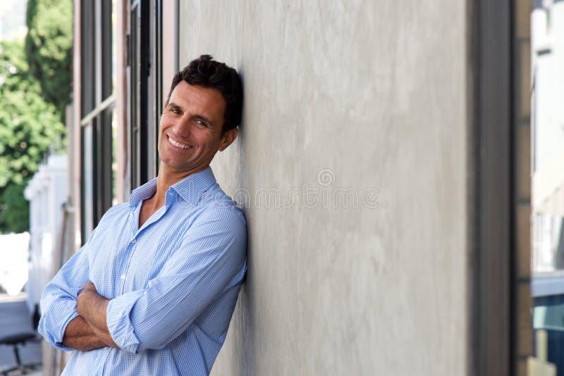 Stilig mogen man som ler och lutar mot väggen arkivbild