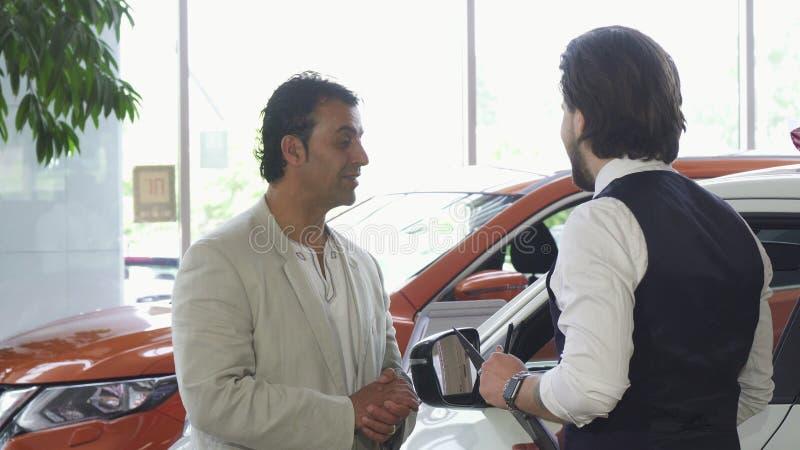 Stilig mogen man som väljer en ny bil på återförsäljaren royaltyfria foton