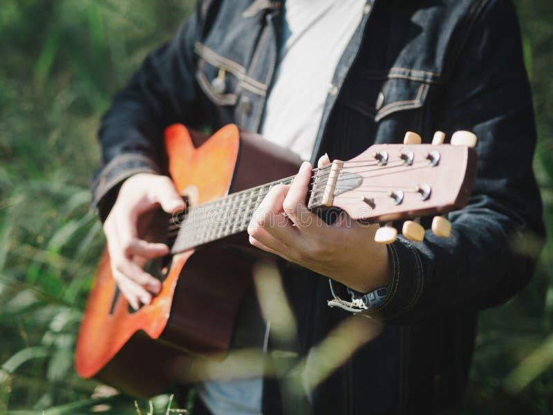 Stilig musiker som spelar den akustiska gitarren på bakgrunden för suddighet för gräsfält Världsmusikdag musik och instrumentbegr royaltyfri bild