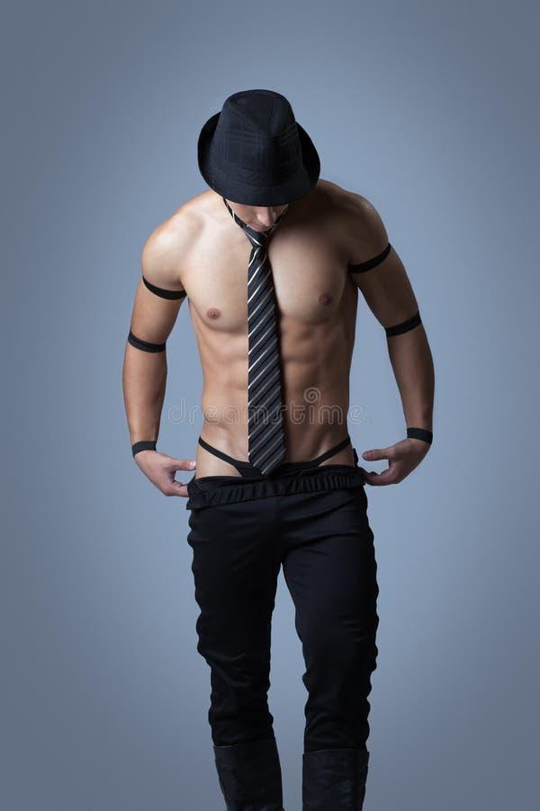 Stilig muskulös grabb som av tar kläder fotografering för bildbyråer