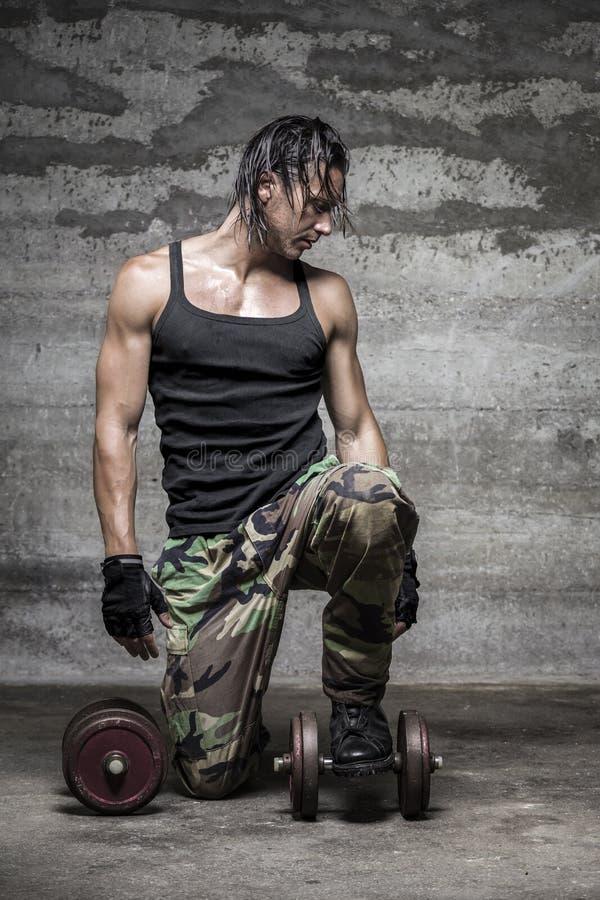 Stilig muskulös man på hans garage royaltyfri fotografi
