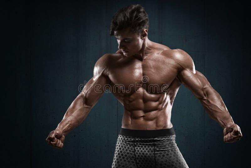 Stilig muskulös man på väggbakgrund, format buk- Stark manlig naken torsoabs arkivfoto