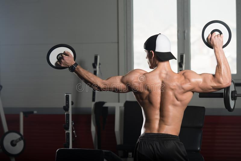 Stilig muskulös man som böjer muskler med vikter royaltyfri foto