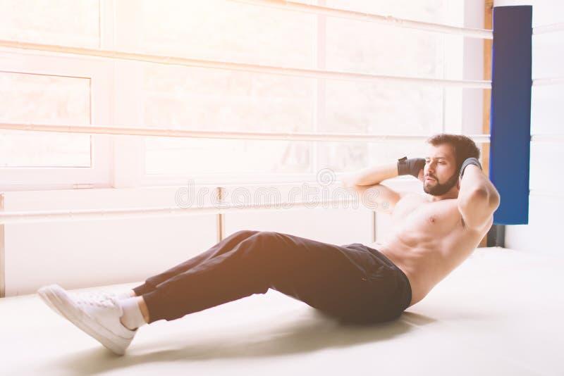 Stilig muskulös man som gör sitta-UPS på ett trägolv arkivfoto