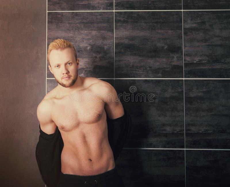 Stilig muskulös manlig modell nära väggen royaltyfri fotografi