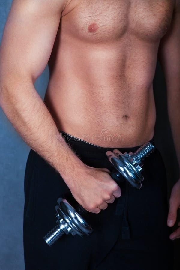 Stilig muskulös manlig modell som gör övning med hantlar royaltyfria foton
