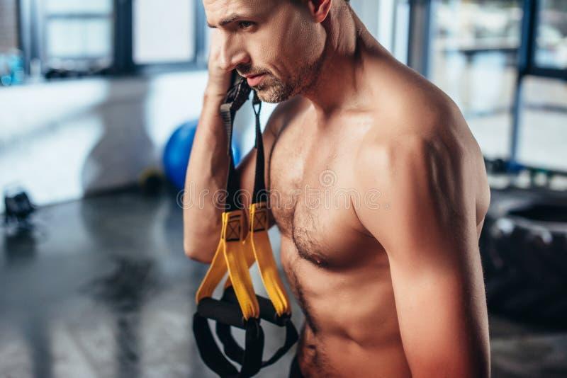 stilig muskulös shirtless idrottsman som rymmer motståndsmusikband royaltyfri fotografi