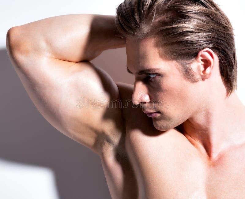 Stilig muskulös ung man som från sidan ser. arkivfoton
