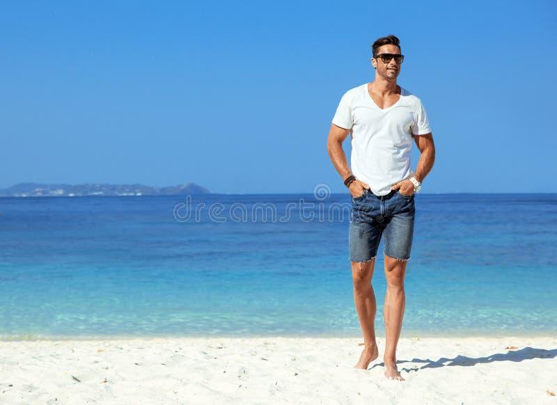 Stilig muskul?s man som kopplar av p? en tropisk strand royaltyfri fotografi