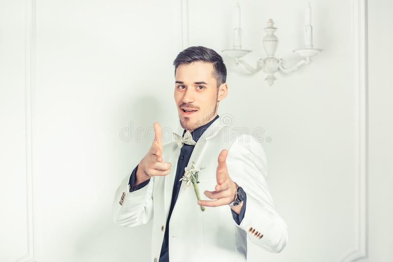 Stilig nöjd brudgum som pekar på kameran royaltyfri foto