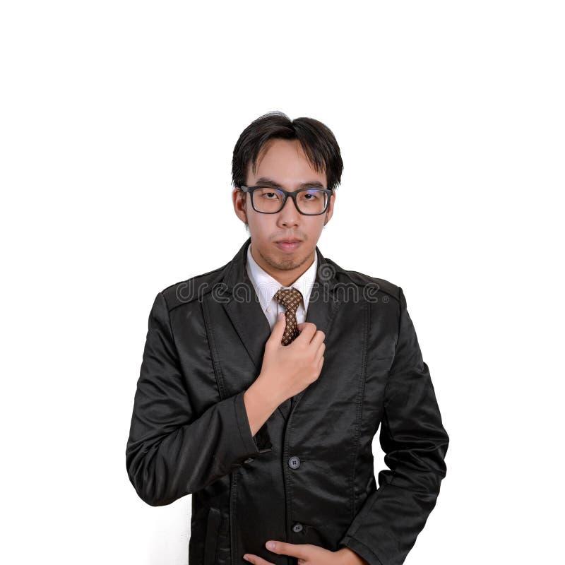 Stilig oavkortad dräkt för ung man som justerar hans slips och lookin arkivbild