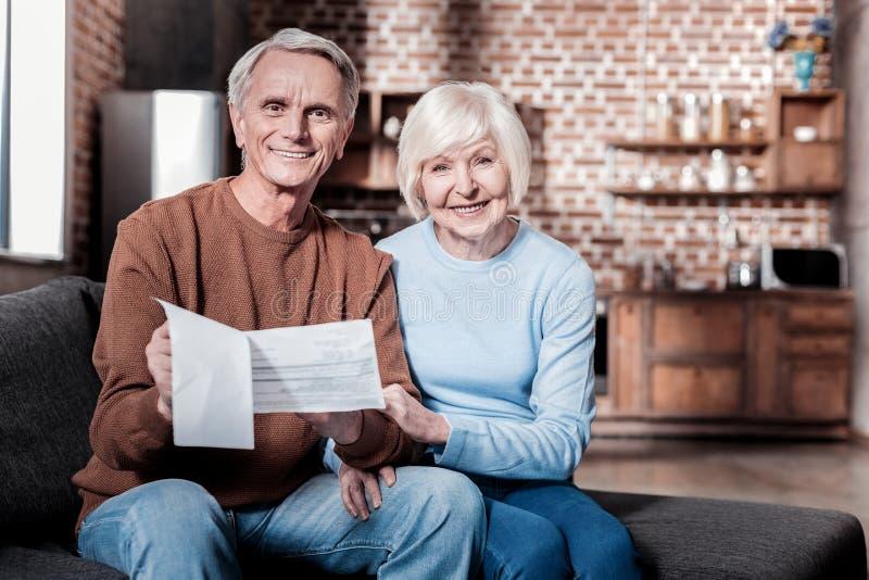 Stilig pensionär som håller dokument i händer arkivbilder