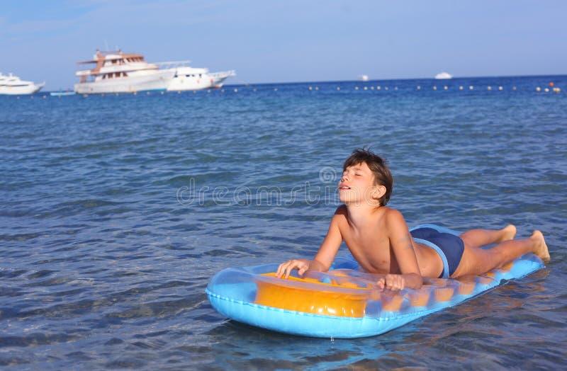Stilig pojke i baddräkt med uppblåsbara matress på det blått arkivfoton