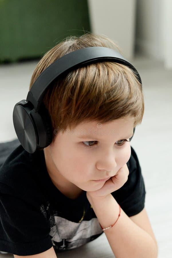 Stilig pojke i hörlurar som lyssnar till musik arkivbilder