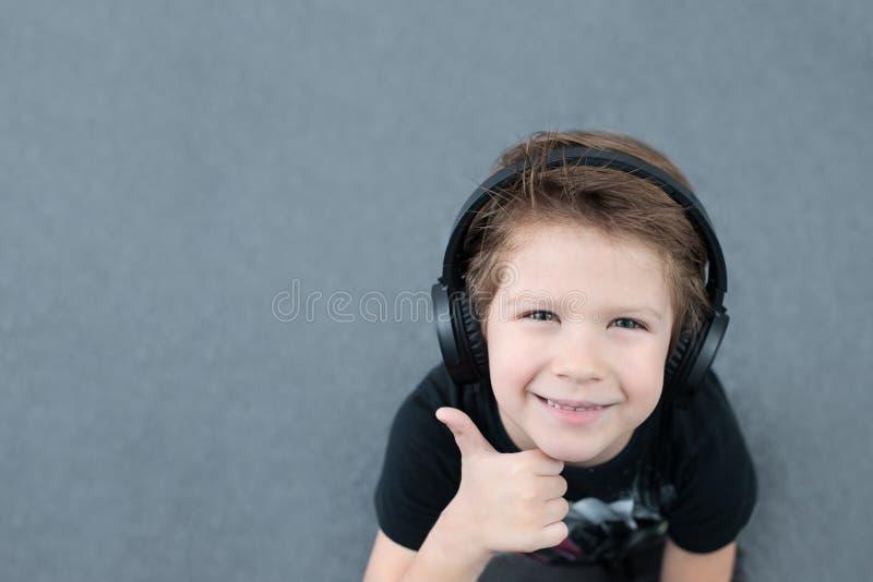 Stilig pojke i hörlurar som lyssnar till musik arkivfoto