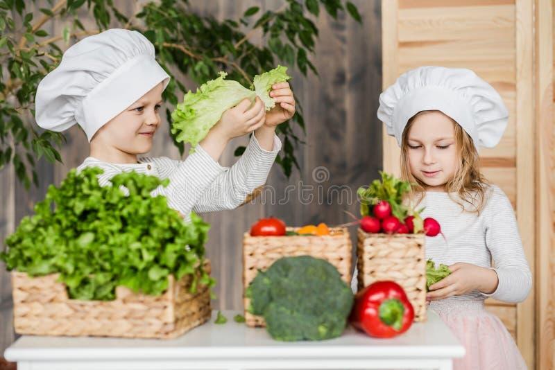 Stilig pojke och härlig ung flicka som spelar i kökkockarna sund mat Grönsaker arkivbilder