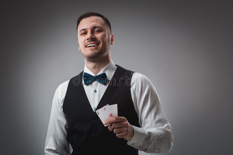 Stilig pokerspelare med två överdängare i hans händer royaltyfri foto