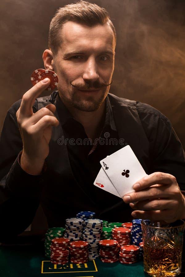 Stilig pokerspelare med två överdängare i hans händer och chiper som mycket sitter på pokertabellen i ett mörkt rum av cigarettrö royaltyfri foto