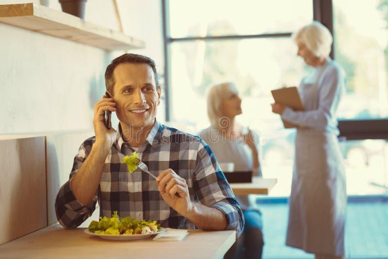 Stilig positiv man som äter en sallad arkivfoto