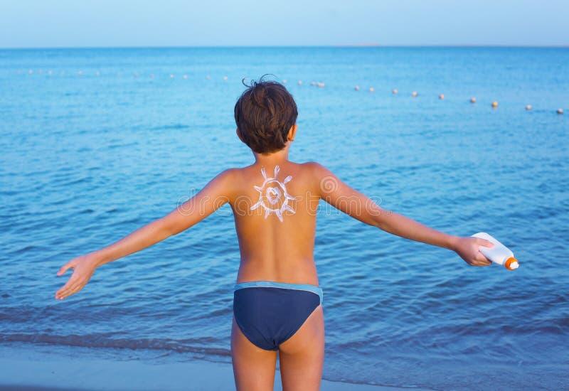 Stilig preteenpojke med den anti-teckningen för solbrännakrämsol på hans arkivfoton
