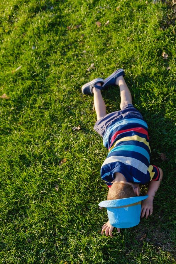 Stilig pys som ligger på gräs Den lilla drömmaren ligger i äng med hatten Barn i natur utanför stad Bekymmerslös semester arkivfoton