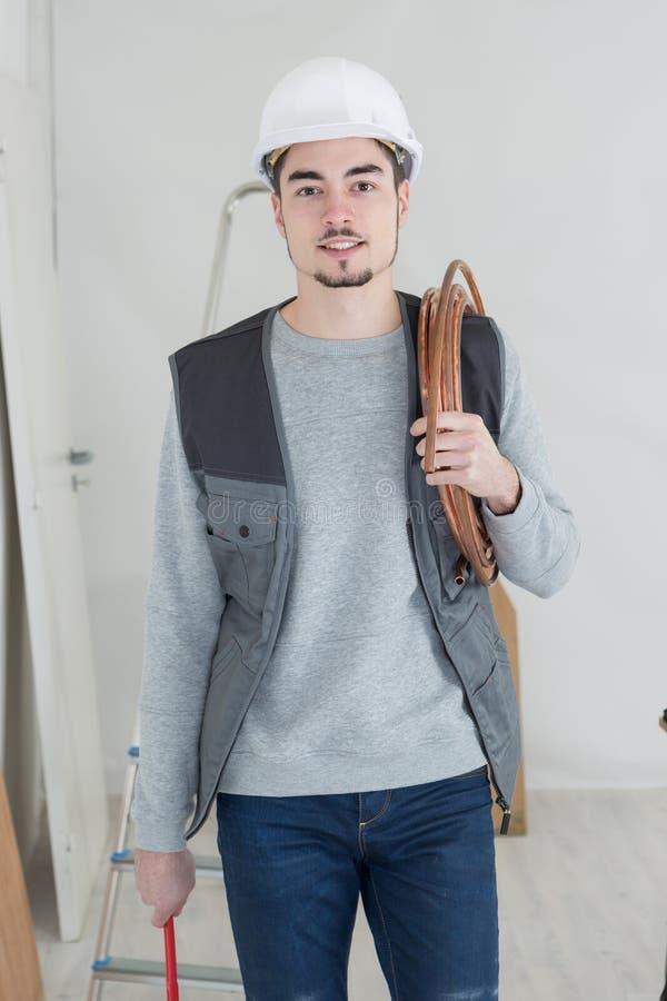 Stilig rörmokare för stående med den justerbara skiftnyckeln och röret royaltyfri fotografi