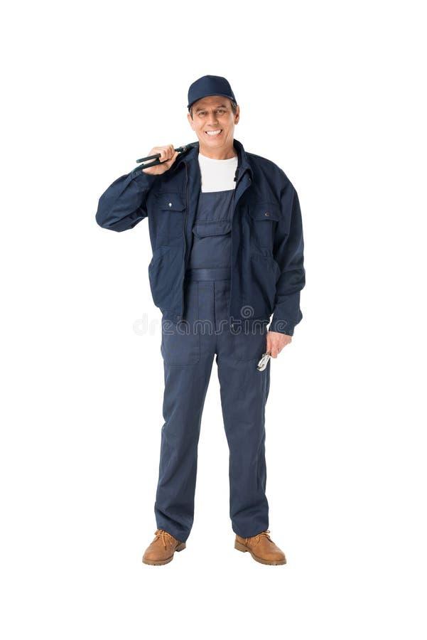 Stilig rörmokare i overaller som rymmer justerbara skiftnycklar royaltyfri foto