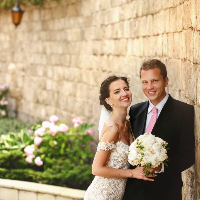 Stilig romantisk brudgum och härlig brunettbrud som nära poserar fotografering för bildbyråer