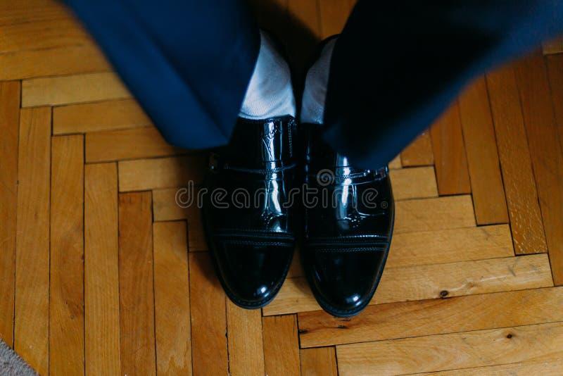 Stilig säker brudgum i blåttdräkten som sätter på svarta skor, närbild royaltyfri bild