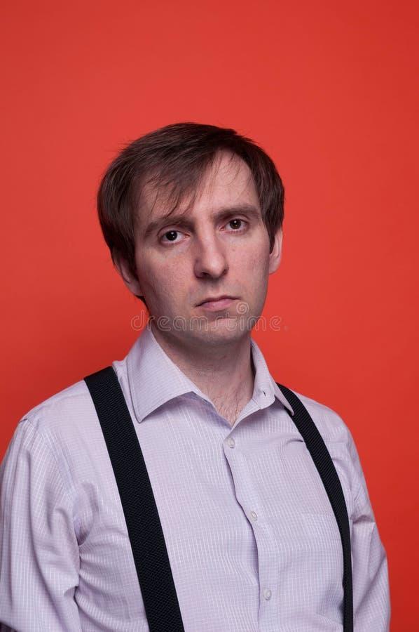 Stilig säker man i rosa skjorta och svarta suspenderen som ser kameran på orange bakgrund royaltyfria bilder